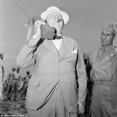 churchill-smokes-a-cigar-as-he-holds-a-radio-to-his-ear-and-watches-the-descent-of-american-paratroopers-during-his-visit-at-fort-jackson-south-carolina