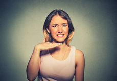 angry-young-woman-gesturing-hand-to-stop-talking-cut-out-will-take-your-head-off-isolated-gray-background-63637067